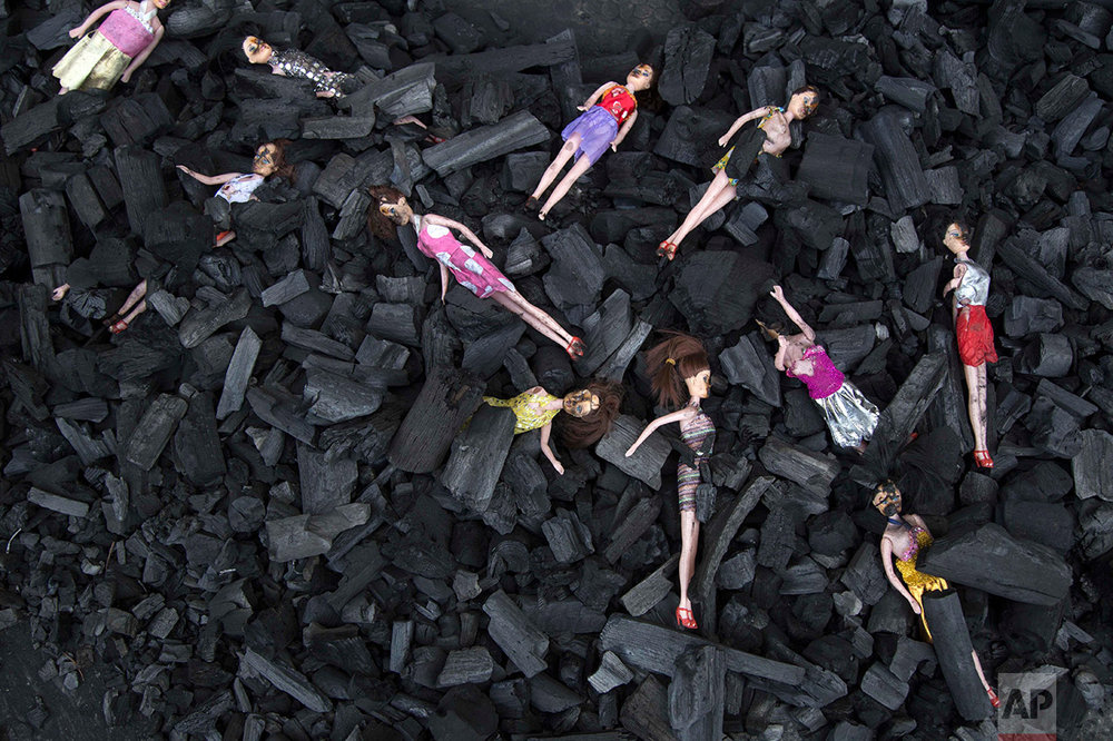 In this March 9, 2017 photo, charred-stained dolls placed on a bed of charcoal are part of an artists' installation placed at the front gate of the presidential house in remembrance of the victims of a fire at the Virgen de la Asunción Safe Home, in Guatemala City. The girls' hell at the government-run home began long before the deadly fire, as documented in several warnings from four different agencies. At least two orders for closure were ignored. (AP Photo/Luis Soto)