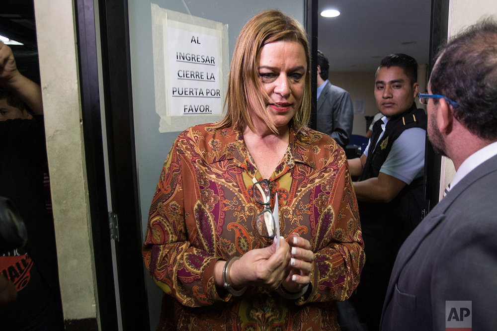 Former Social Welfare Deputy Secretary Anahi Keller is escorted by police at a police station after her detention in connection with the fire at a children's shelter that killed 40 girls in Guatemala City, Monday, March 13, 2017. (AP Photo/Moises Castillo)