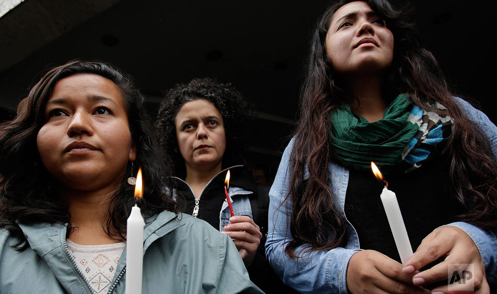 Women hold candles outside Guatemala's embassy during a demonstration demanding justice for the 40 Guatemalan girls killed last week in the fire at a state-run children's shelter, in Quito, Ecuador, Thursday, March 16, 2017. (AP Photo/Dolores Ochoa)