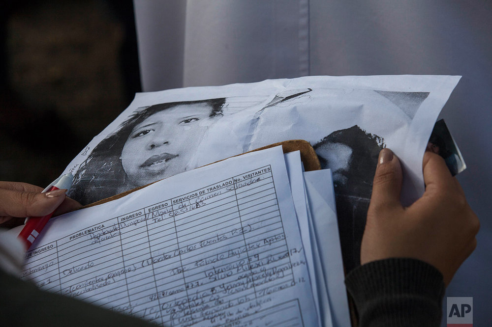 In this March 8, 2017 photo, a doctor holds photos of victims of the Virgen de la Asuncion Safe Home fire, as relatives try to identify them, outside the Roosevelt Hospital in Guatemala City. Forty girls died in the tragedy after they lit several mattress during a protest. (AP Photo/Moises Castillo)