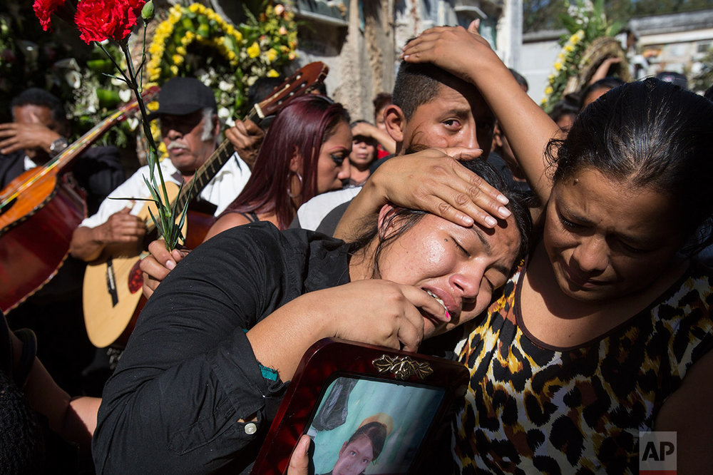 In this March 17, 2017 photo, Shirley Palencia weeps during the burial service for 17-year-old sister Kimberly Palencia Ortiz, who died in the Virgen de la Asunción Safe Home fire, at the cemetery in Guatemala City. Authorities said the fire that swept through parts of the institution when mattresses were set ablaze during a protest by girls protesting conditions at the overcrowded youth shelter. (AP Photo/Moises Castillo)