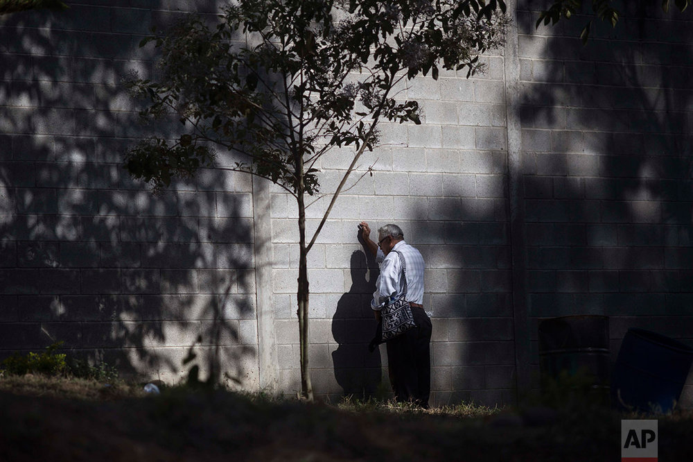 A man prays on the wall outside the Virgen de la Asunción children's shelter, in San Jose Pinula, Guatemala, Wednesday, March 8, 2017. At least 19 people have died after a fire at the shelter, which was created to house children who were victims of abuse, homelessness or who had completed sentences at youth detention centers and had nowhere else to go, the spokesman for Guatemala's volunteer fire departments said. (AP Photo/Luis Soto)