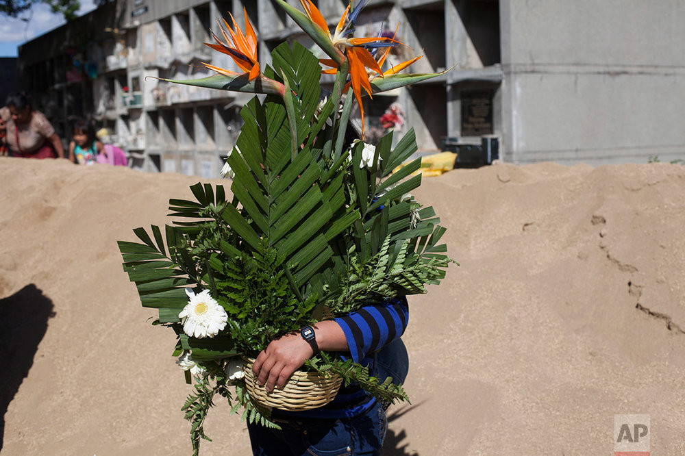A woman holds a flowers bouquet during the burial of 14-year-old Madelyn Patricia Hernandez Hernandez, a girl who died in a fire at the Virgin of the Assumption Safe Home, at the Guatemala City's cemetary, Friday, March 10, 2017. Families began burying some of the 36 girls killed in a fire at an overcrowded government-run youth shelter in Guatemala as authorities worked to determine exactly what happened. (AP Photo/Moises Castillo)