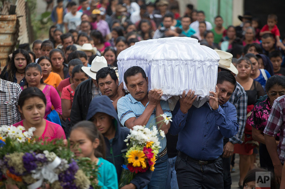 In this March 12, 2017 photo, people carry the coffin of 14-year-old Ana Roselia Perez Junay, who died in the fire at Virgen de la Asunción Safe Home, to the cemetery in Zaragoza, Guatemala. The majority of the children at the shelter had committed no crime, but were youths sent there by the courts for various reasons. Most came from families so poor they could not afford the $50 lawyers' fees to get their children out. (AP Photo/Moises Castillo)
