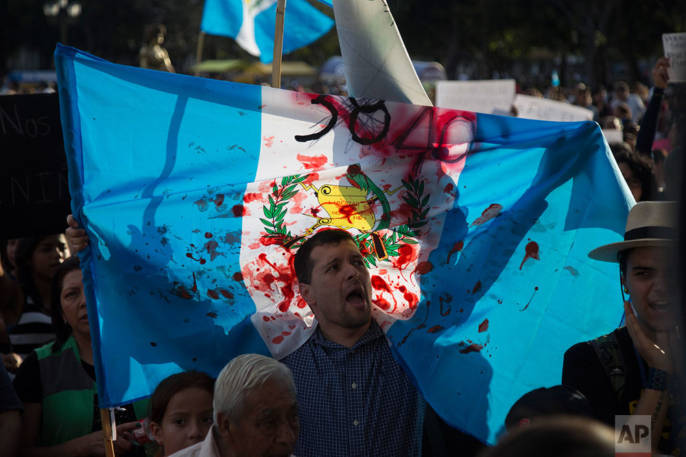 A man holds up a Guatemalan national flag stained with fake blood during a protest demanding justice for the girls who perished in the youth shelter fire, in front of the National Palace in Guatemala City, Saturday, March 11, 2017. A key Guatemalan official was ordered not to leave the country Saturday as the death toll rose to 39 girls in a fire that began when mattresses were set ablaze during a protest by residents of the youth shelter. (AP Photo/Luis Soto)
