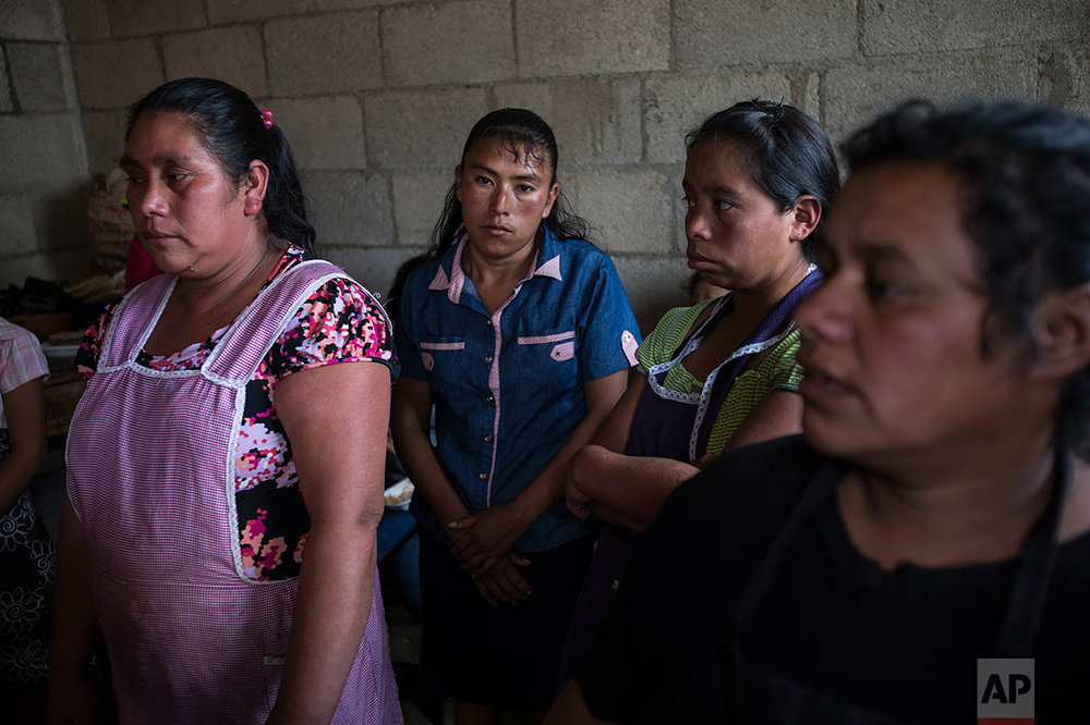Women attend the wake of 14-year-old Ana Roselia Perez Junay, who died in a fire at a children's shelter, inside her mother's home in Zaragoza, Guatemala, Sunday, March 12, 2017. The death toll in the March 8 fire rose to 40 on Sunday with the announcement that another girl has died of burns. (AP Photo/Moises Castillo)