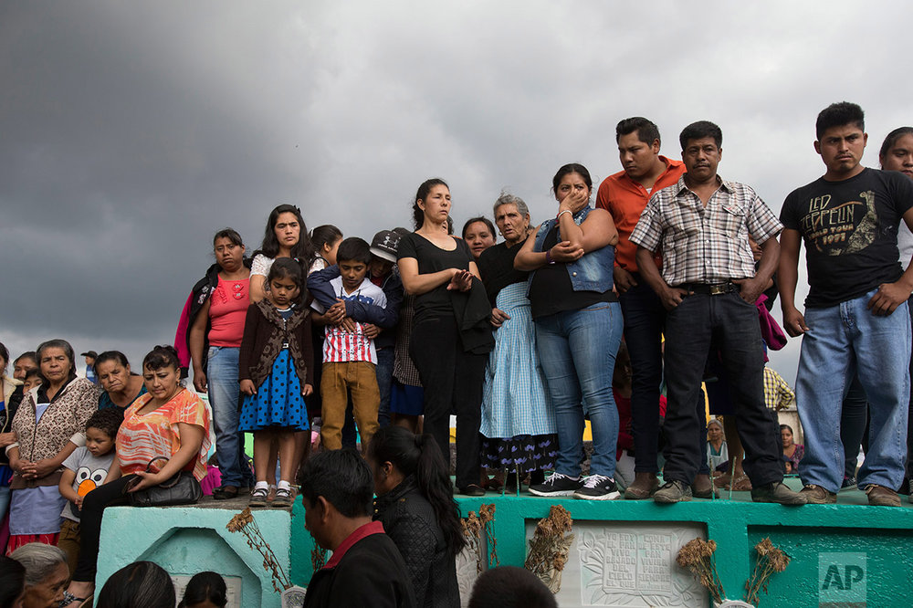 In this March 12, 2017 photo, people attend the burial of 14-year-old Ana Roselia Perez Junay, who died in a fire at the Virgen de la Asunción Safe Home, at the cemetery in Zaragoza, Guatemala. The fire on March 8th that killed 40 girls at the shelter started when girls took a match to a foam mattress to protest the abuse they had suffered there. (AP Photo/Moises Castillo)