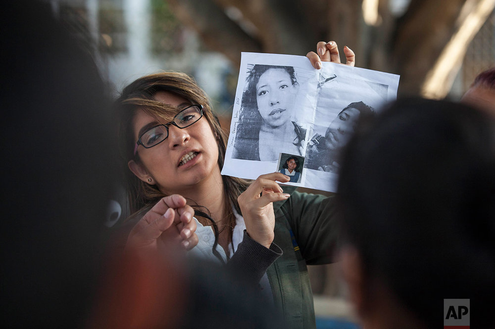 In this March 8, 2017 photo, a doctor shows photos of the victims in an attempt to identify them after a fire at the Virgen de la Asuncion Safe Home, outside the Roosevelt Hospital in Guatemala City. When firefighters entered the home for troubled youths, they discovered more than two dozen girls on the floor of a locked room, most of them dead. (AP Photo/Moises Castillo)