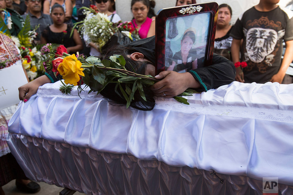 In this March 17, 2017 photo, Shirley Palencia mourns over the coffin containing the remains of her 17-year-old sister Kimberly Palencia Ortiz, who died in the Virgen de la Asuncion Safe Home fire, at the cemetery in Guatemala City. Palencia Ortiz had been a ward of the state for nearly a year. Her father was in prison, her mother had disappeared, and her grandmother did not have the means to take care of her. (AP Photo/Moises Castillo)