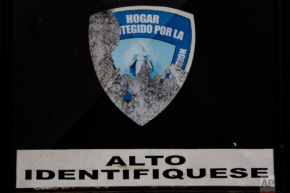 "In this March 15, 2017 photo, stickers, one with an image of the Virgin Mary with a partial text that reads in Spanish ""Home protected by"" and another sign that reads ""Stop, identify yourself,"" are stuck on the entrance to Virgen de la Asuncion Safe Home, in San Jose Pinula, Guatemala. On March 7, about 60 girls escaped from the shelter by jumping from the roof of the facility to the wall, and from there into the trees. (AP Photo/Moises Castillo)"