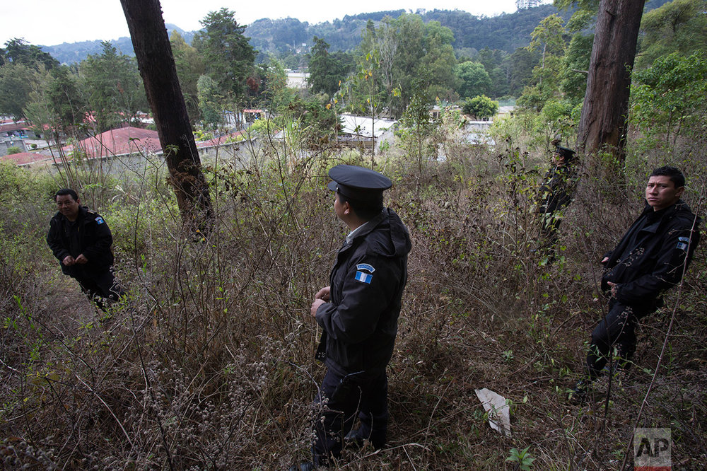 In this March 15, 2017 photo, police stand guard in the woods near the Virgen de la Asuncion Safe Home, in San Jose Pinula, Guatemala. The children's shelter, located on a hill 14 miles southeast of Guatemala City, protected by high walls and barbed wire, is surrounded by an idyllic pine forest covered with mist every morning. The forest and ravines have offered hiding places for more than 100 children who have escaped what they consider a jail. (AP Photo/Moises Castillo)
