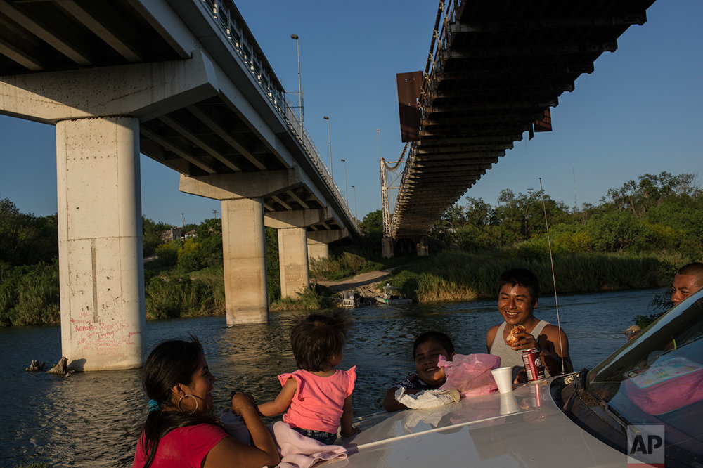A family enjoys a picnic on the banks of the Rio Grande river in Miguel Aleman, Tamaulipas state, Mexico, Wednesday, March, 22, 2017, located across the river from Roma, Texas. (AP Photo/Rodrigo Abd)