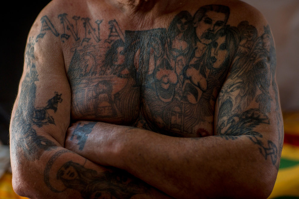 "Mexican migrant Juan Parras, 65, covered in tattoos, poses for a portrait in the dormitory at the migrant shelter ""Senda de Vida"" in Reynosa, Mexico, Wednesday, March 22, 2017. Parras said he was deported one year ago from California, where he left behind three sons, and he plans to try to return but it's more difficult now to get past U.S. security. Regarding the proposed border wall, Parras said ""Mexico is not going to pay for the wall."" (AP Photo/Rodrigo Abd)"