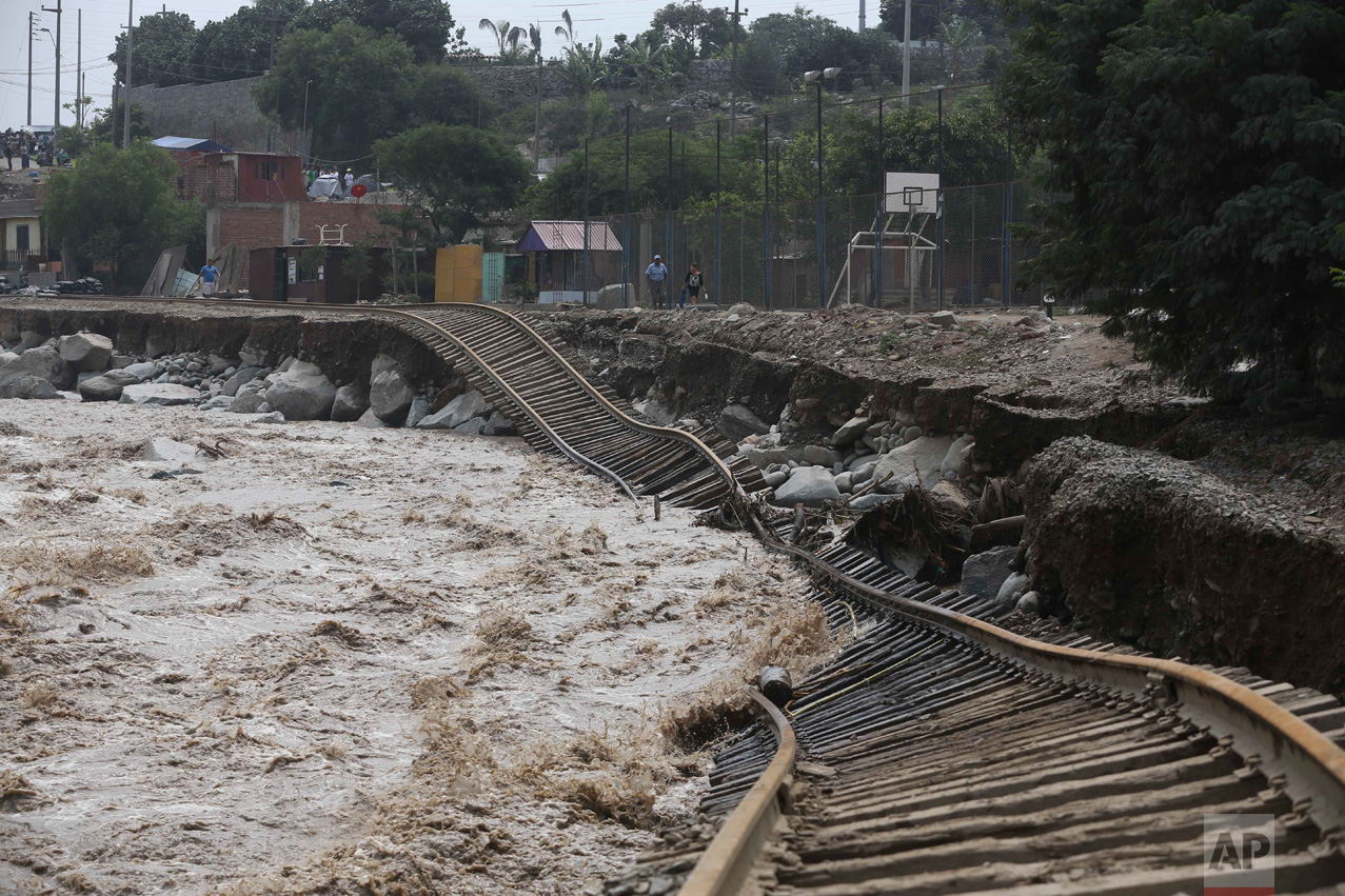 Train tracks are twisted into a flooded river in the Chosica district of Lima, Peru, on Sunday, March 19, 2017. Intense rains and mudslides have wrought havoc around the Andean nation and caught residents in Lima, a desert city of 10 million where it almost never rains, by surprise. (AP Photo/Martin Mejia)