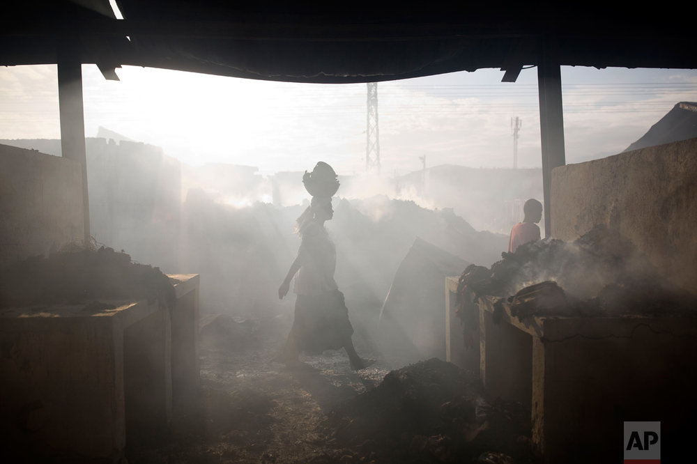 A merchant walks through smoke at a market in Port-au-Prince, Haiti, on Monday, March 20, 2017. A fire damaged the biggest central market in the center of the Haitian capital. (AP Photo/Dieu Nalio Chery)
