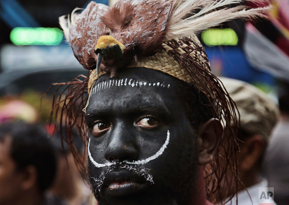 A Papuan activist with traditional headwear which includes a stuffed bird of paradise attends a protest against U.S. mining giant Freeport-McMoRan Copper & Gold Inc. in Jakarta, Indonesia, Monday, March 20, 2017. A group of activists staged the protest demanding the New Orleans-based mining company close its mine in Papua province saying that it siphons off the region's wealth and gives it little in return. (AP Photo/Achmad Ibrahim)