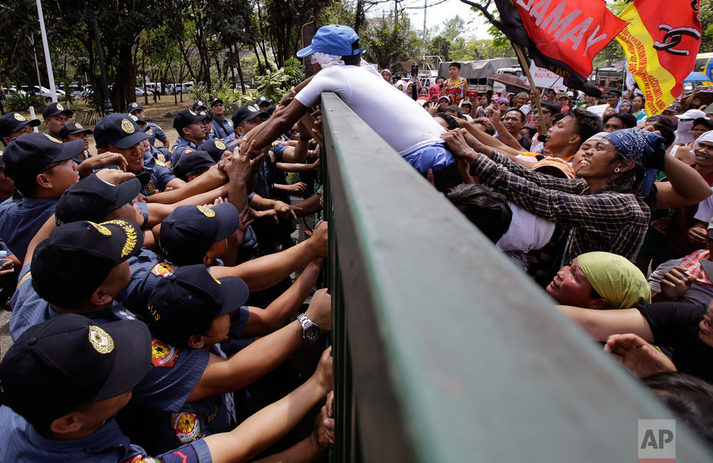 "Police officers stop a demonstrator from trying to open the gates of the National Housing Authority offices during a rally in Quezon City, Philippines, northeast of Manila, on Friday, March 24, 2017. The group is protesting the possible eviction to hundreds of informal settlers who have occupied a housing community for police and military in northern province of Bulacan. In a statement, the occupants deemed the eviction notice a ""violation of urban poor rights"" and vowed to resist any move to evict them. (AP Photo/Aaron Favila)"