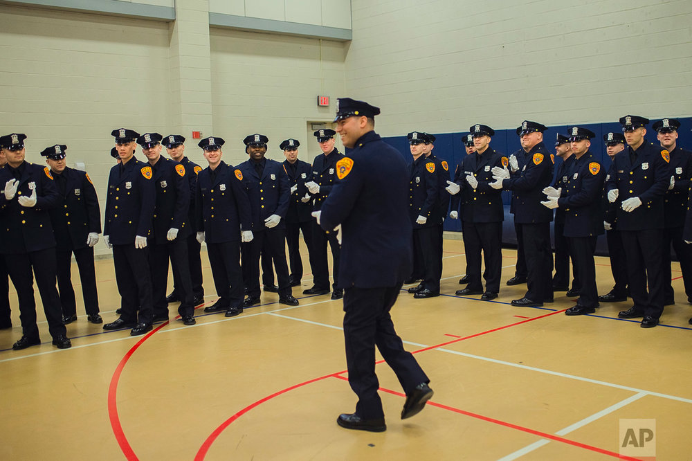 Matias Ferreira, center, arrives as his colleagues salute him while they prepare to march during their graduation from the Suffolk County Police Department Academy at the Health, Sports and Education Center in Suffolk, Long Island, New York, Friday, March 24, 2017. (AP Photo/Andres Kudacki)