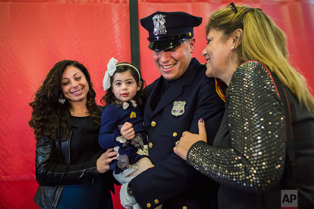 Matias Ferreira, center, celebrates with his 2-year-old daughter, his wife, left, and his mother during his graduation from the Suffolk County Police Department Academy at the Health, Sports and Education Center in Suffolk, Long Island, New York, Friday, March 24, 2017. Matias Ferreira, a former U.S. Marine Corps lance corporal who lost his legs below the knee when he stepped on a hidden explosive in Afghanistan in 2011, is joining a suburban New York police department. The 28-year-old graduated Friday from the Suffolk County Police Academy on Long Island following 29 weeks of training. (AP Photo/Andres Kudacki)