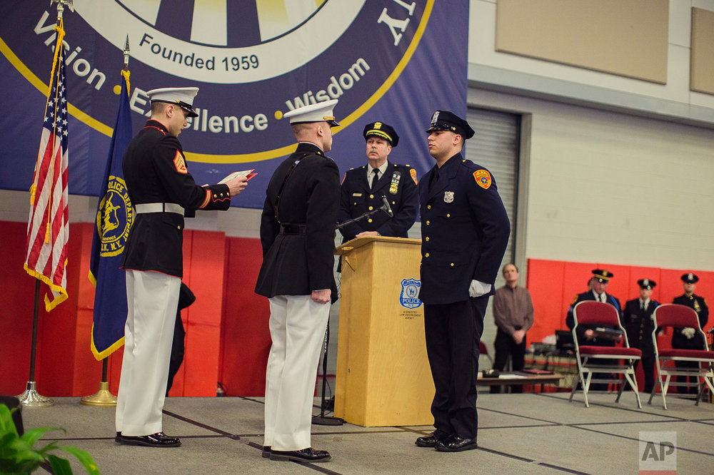 Matias Ferreira, center, receives his diploma during his graduation from the Suffolk County Police Department Academy at the Health, Sports and Education Center in Suffolk, Long Island, New York, Friday, March 24, 2017.(AP Photo/Andres Kudacki)
