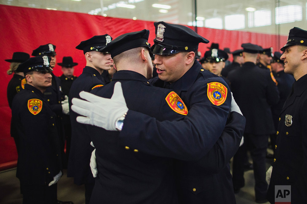 Matias Ferreira, center, hugs his colleague as they prepare to march during their graduation from the Suffolk County Police Department Academy at the Health, Sports and Education Center in Suffolk, N.Y., Friday, March 24, 2017. Ferreira, a former U.S. Marine Corps lance corporal who lost his legs below the knee when he stepped on a hidden explosive in Afghanistan in 2011, is joining a suburban New York police department. The 28-year-old graduated Friday from the Suffolk County Police Academy on Long Island following 29 weeks of training. (AP Photo/Andres Kudacki)