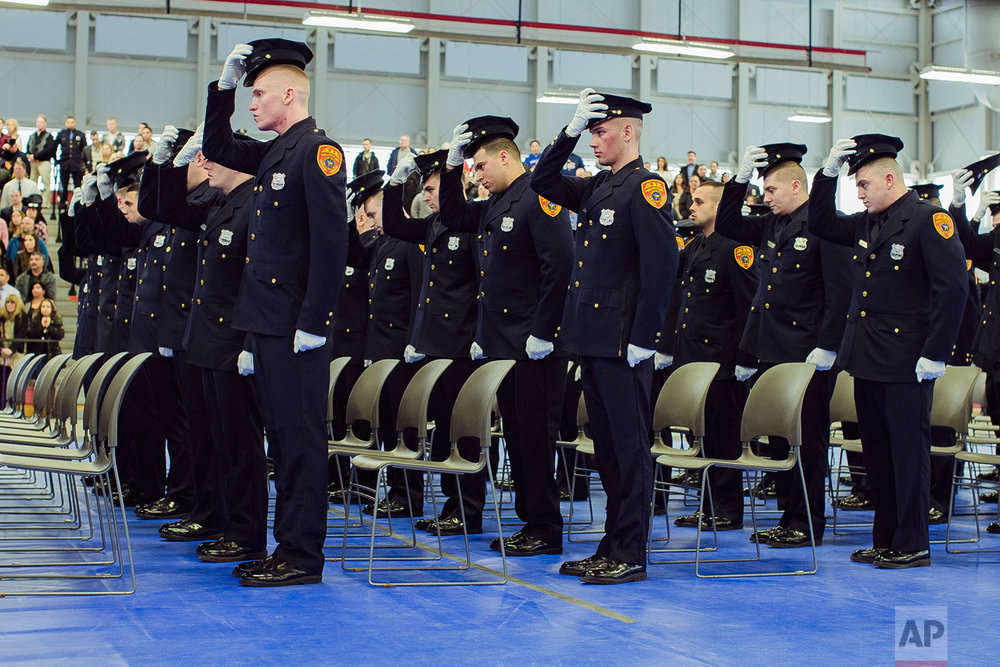 Matias Ferreira, second row, second, and his colleagues take off his hat during their graduation from the Suffolk County Police Department Academy at the Health, Sports and Education Center in Suffolk, N.Y., Friday, March 24, 2017.(AP Photo/Andres Kudacki)
