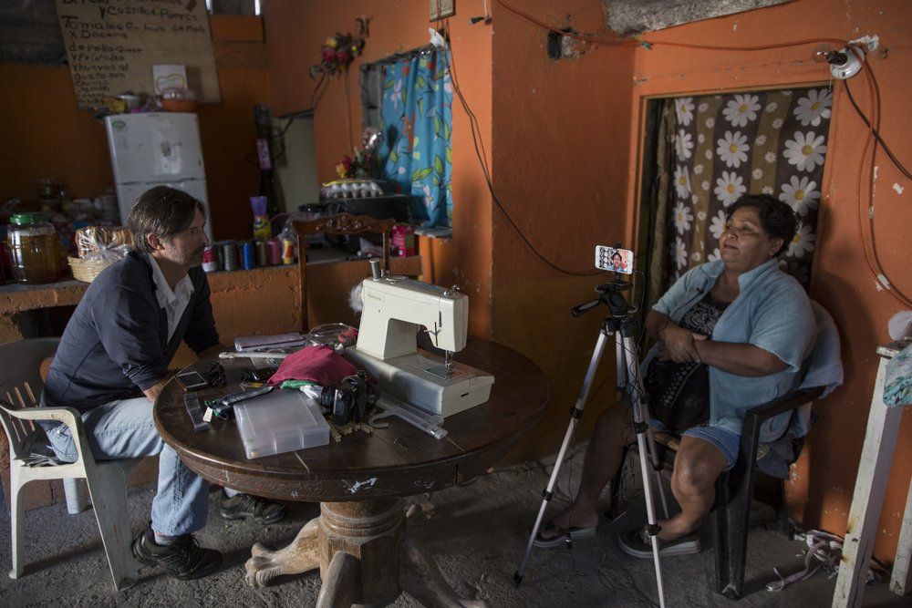 AP journalist Christopher Sherman interviews Jesus Esteban Cruz inside her home in Reynosa, Mexico, Wednesday, March 22, 2017, across the border from McAllen, Texas. (AP Photo/Rodrigo Abd)