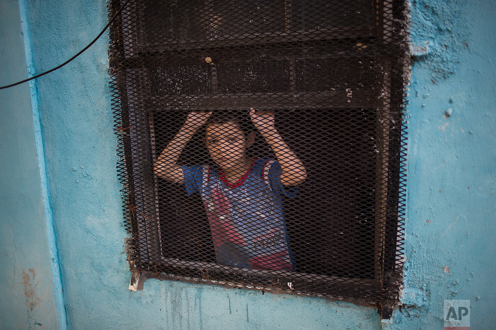 A boy peeks out of the window of his house in Nuevo Laredo, Tamaulipas state, Mexico, across the border from Laredo in the U.S, Friday March 24, 2017.(AP Photo/Rodrigo Abd)