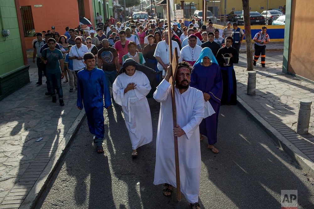 Cuban migrant Rudy Rivero leads a religious procession, adapted to reflect the plight of immigrants, in Nuevo Laredo, Tamaulipas state, Mexico, Friday, March 24, 2017, across the border from Laredo, Texas. (AP Photo/Rodrigo Abd)