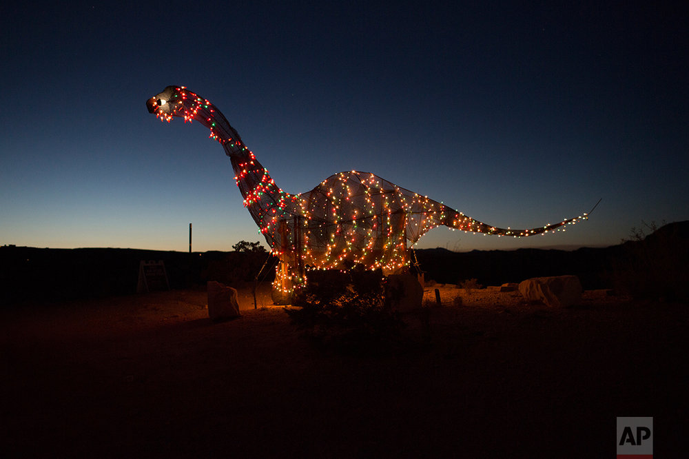 A dinosaur statue stands outside a store off the highway in Terlingua, Texas, near the US-Mexico border, Monday, March 27, 2017. (AP Photo/Rodrigo Abd)