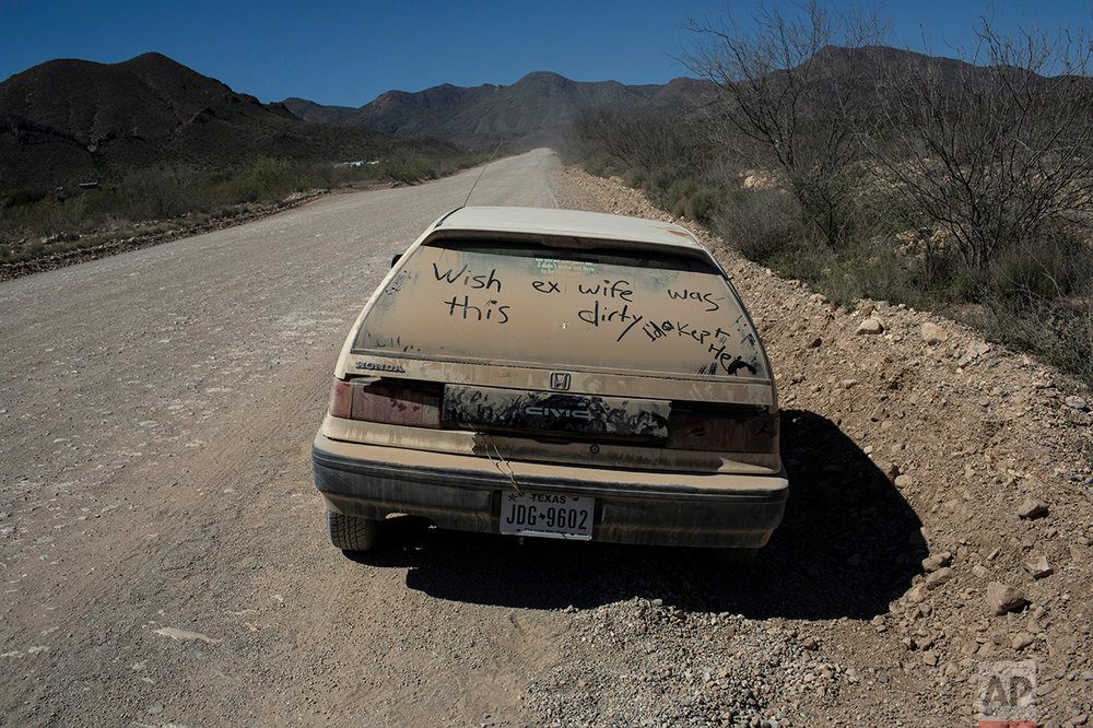 A car with a message written on its dusty back window sits abandon on the side of a road in Terlingua, Texas, near the US-Mexico border, Monday, March 27, 2017. (AP Photo/Rodrigo Abd)