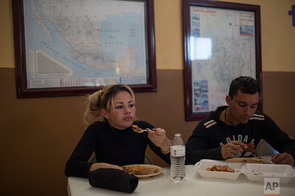 "Cuban migrants Chaday Sanchez and her boyfriend Rodolfo Munoz eat dinner at the migrant shelter ""Casa del Migrante"" in Nuevo Laredo, Tamaulipas state, Mexico, Saturday, March 25, 2017, across the border from Laredo, Texas. (AP Photo/Rodrigo Abd)"