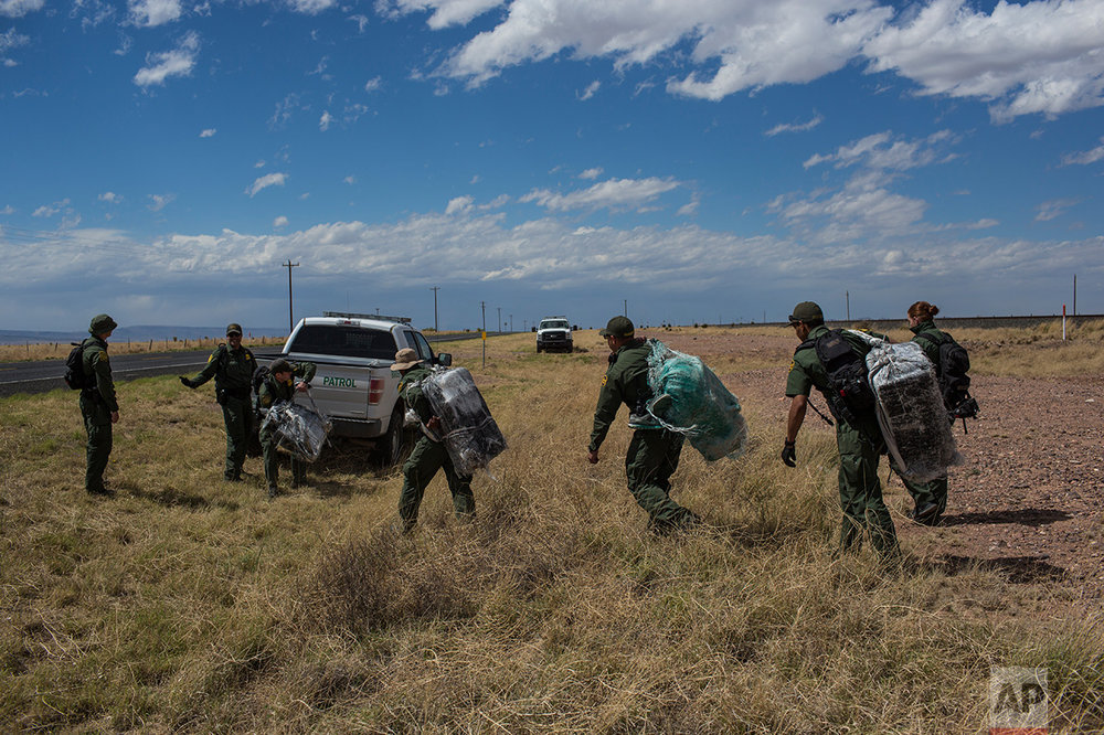 "U.S. Border Patrol agents carry bales of marijuana they found along the highway near Ryan, Texas, about 20 miles from the US-Mexico border, Tuesday, March 28, 2017. One agent said ""They (the smugglers) just leave it and come back another day. It's going to be sad when they come back for it.""  Drug interdiction is a core mission for the Border Patrol. (AP Photo/Rodrigo Abd)"
