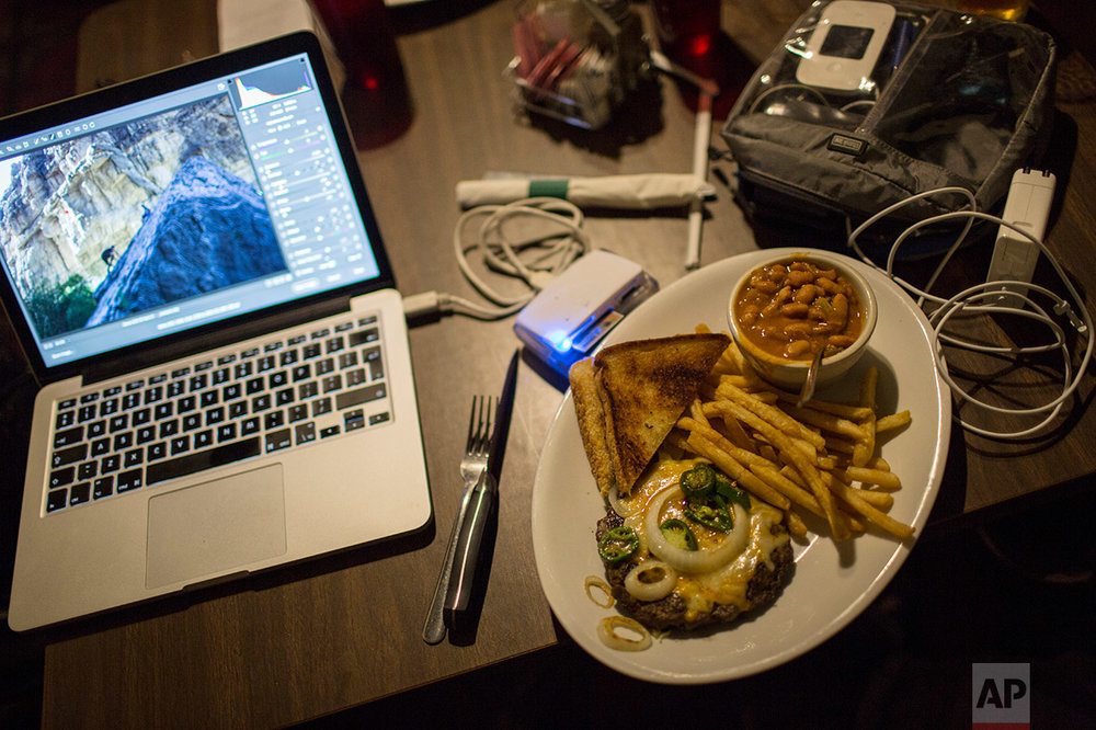 An open-faced jalapeÒo hamburger with fries, beans and toast by Rodrigo Abd's computer as he edits while eating dinner in Terlingua, Texas, near the US-Mexico border, Monday, March 27, 2017. (AP Photo/Rodrigo Abd)