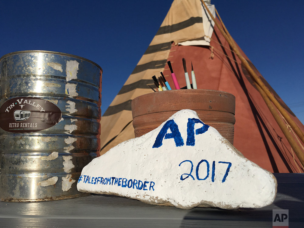 A rock painted by AP journalist Christopher Sherman, at the invitation of Tin Valley Retro Rentals, where overnight guests are encouraged to leave their mark in their desert playground in Terlingua, Texas, near the US-Mexico border, Monday, March 27, 2017. The rental options are on about 90 acres of desert, where Airstream trailers and old buses are converted into quarters. People can also sleep in one of two tipis. (AP Photo/Christopher Sherman)