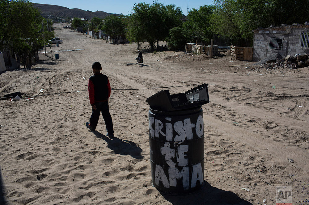 "A boy walks away from the municipal garbage dump where he threw away the casing of an unusable TV, in the Anapra neighborhood of Ciudad Juarez, Mexico, Thursday, March 30, 2017, across the border from Sunland Park, New Mexico. The trash can reads in Spanish ""Christ loves you."" (AP Photo/Rodrigo Abd)"