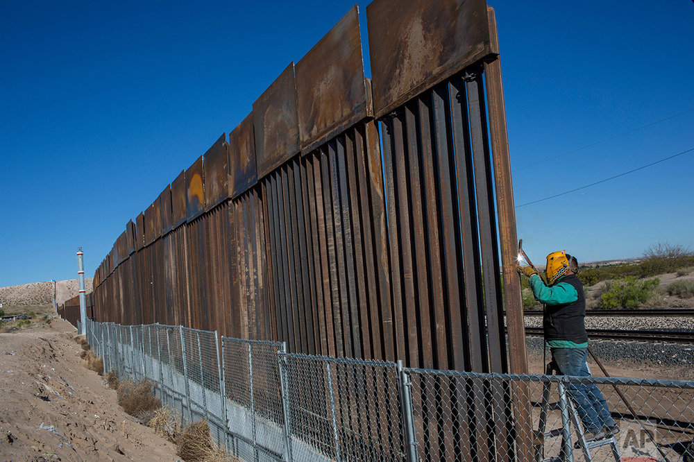 A worker welds a new fence between the Anapra neighborhood of Ciudad Juarez, Mexico, and Sunland Park, New Mexico, Thursday, March 30, 2017. The top three feet or so of the fence, which was planned and started before President Donald Trump's election, are a solid panel of oxidized steel. (AP Photo/Rodrigo Abd)