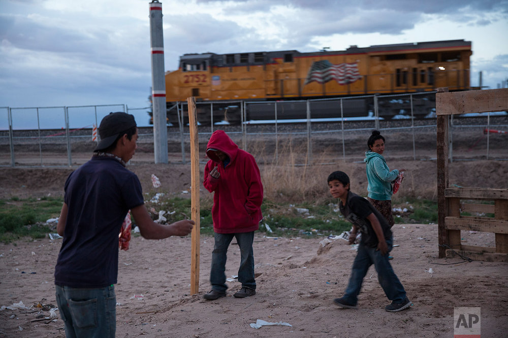Children play a coin toss game in the sand as a train passes behind the fence marking the U.S.-Mexico border, in the Anapra neighborhood of Ciudad Juarez, Mexico, Wednesday, March 29, 2017, across the border from Sunland Park, New Mexico. There are more than 650 miles of fence, wall and vehicle barriers along the nearly 2,000-mile border. (AP Photo/Rodrigo Abd)