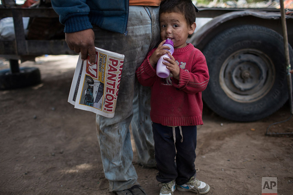 Rohan Ayala stands next to his father outside their home, meters from the fence marking the U.S.-Mexico border in Juarez Valley, Mexico, Wednesday, March 29, 201, across the border from the outskirts of El Paso, Texas. A segment of new fencing is being erected by the U.S. government outside El Paso, Texas, just west of the New Mexico state line. (AP Photo/Rodrigo Abd)