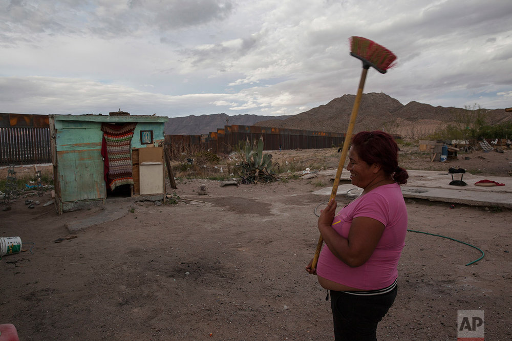 Claudia Sanchez holds a broom outside her shack home in the Anapra neighborhood of Ciudad Juarez, Mexico, Wednesday, March 29, 2017, across the border from Sunland Park, New Mexico. Homes in this area are made of concrete block, wooden pallets, and any sort of recovered material that can withstand the wind and hold back the blowing sand of the dunes. (AP Photo/Rodrigo Abd)
