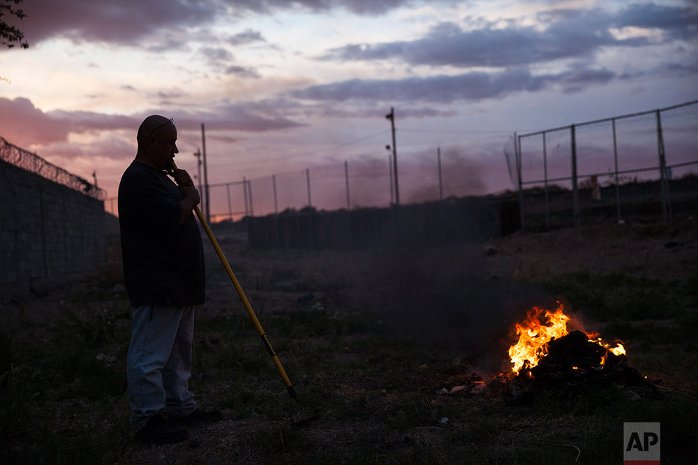 A man burns trash near the border fence in the Anapra neighborhood of Ciudad Juarez, Mexico, late Wednesday, March 29, 2017, across the border from Sunland Park, New Mexico. Residents of Anapra, a neighborhood anchored to the dunes, have fought to get running water, electricity and some paved streets in recent years. (AP Photo/Rodrigo Abd)