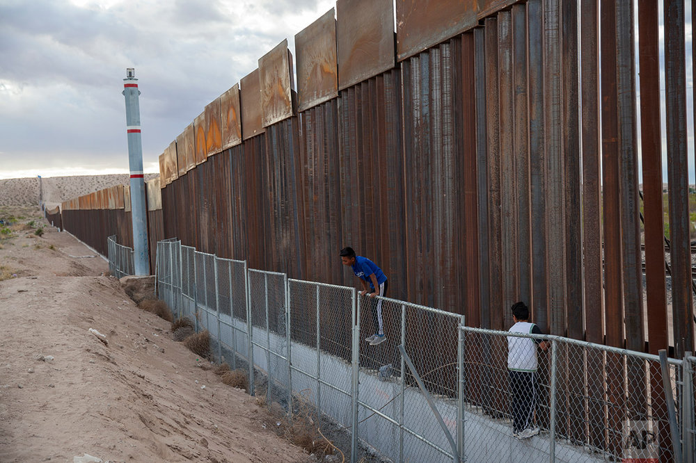 Children play on two fences marking the U.S.-Mexico border, in the Anapra neighborhood of Ciudad Juarez, Mexico, Wednesday, March 29, 2017, across the border form Sunland Park, New Mexico. In Mexico, people have lived and worked in the existing fence's shadow for years. That experience has made them dispassionate toward talk of new construction of a larger wall. (AP Photo/Rodrigo Abd)