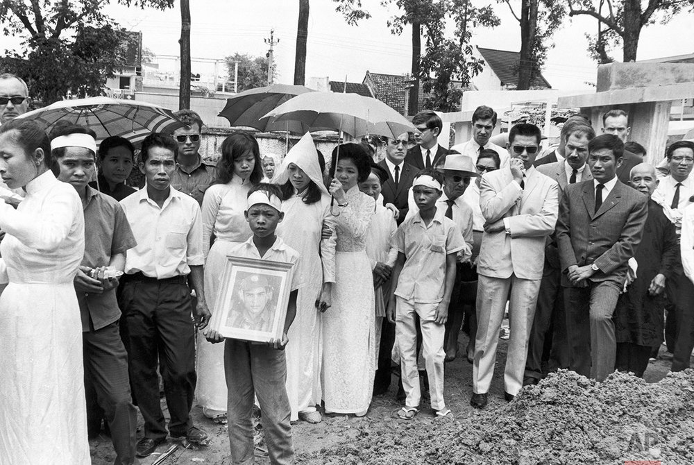 Newsmen and family members attend the funeral for AP photographer Huynh Thanh My, killed on the job, Oct. 1965. At far left wearing head band is his 16-year-old brother Huynh Cong (Nick) Ut. Others include Ed White, Rick Merron, Huynh Thanh My's widow (wearing white hood), Peter Arnett, Dirck Halstead, Neil Sheehan (New York Press), Bill Ha Van Tran (Associated Press), Eddie Adams (AP), Vo Huynh (NBC), Malcolm Brown, Bob Liu (Associated Press) in Vietnam during 1965-1968. (AP Photo)