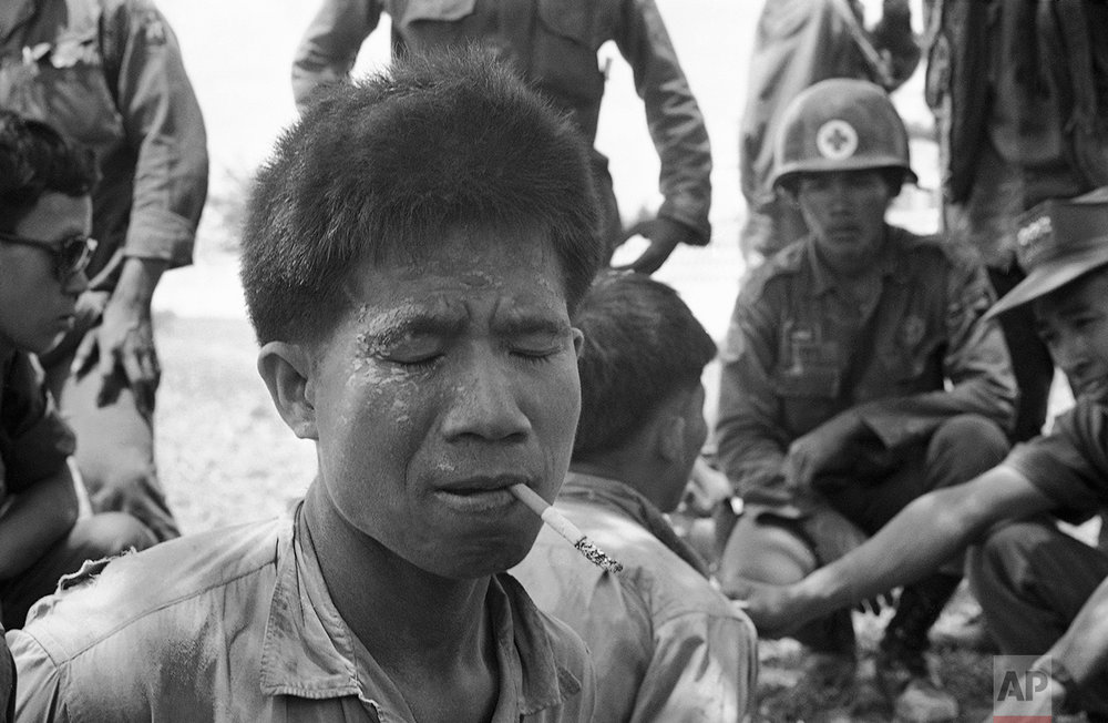The commander of a North Vietnamese army battalion smokes a cigarette given him by South Vietnamese troops after being captured in a firefight North of Prasaut in Eastern Cambodia's Parrot's beak region on May 13, 1970. (AP Photo/Nick Ut)
