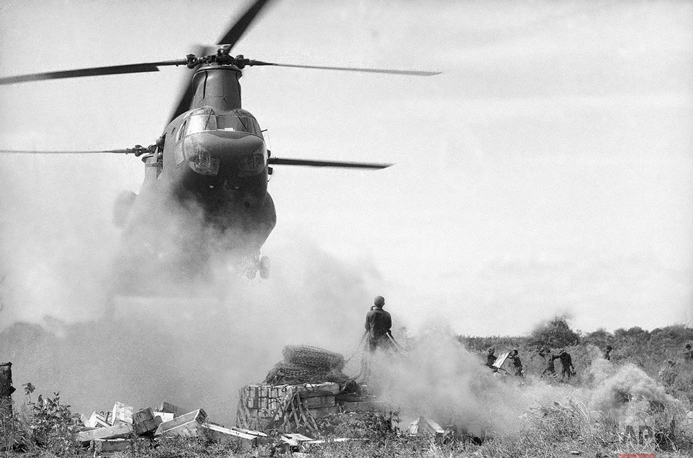 Almost hidden by marker smoke, a South Vietnamese soldier prepares to hook a sling-load onto a twin-rottered Chinook helicopter supporting operations near of Phnom Penh, Cambodia on Dec. 25, 1970. (AP Photo/Nick Ut)