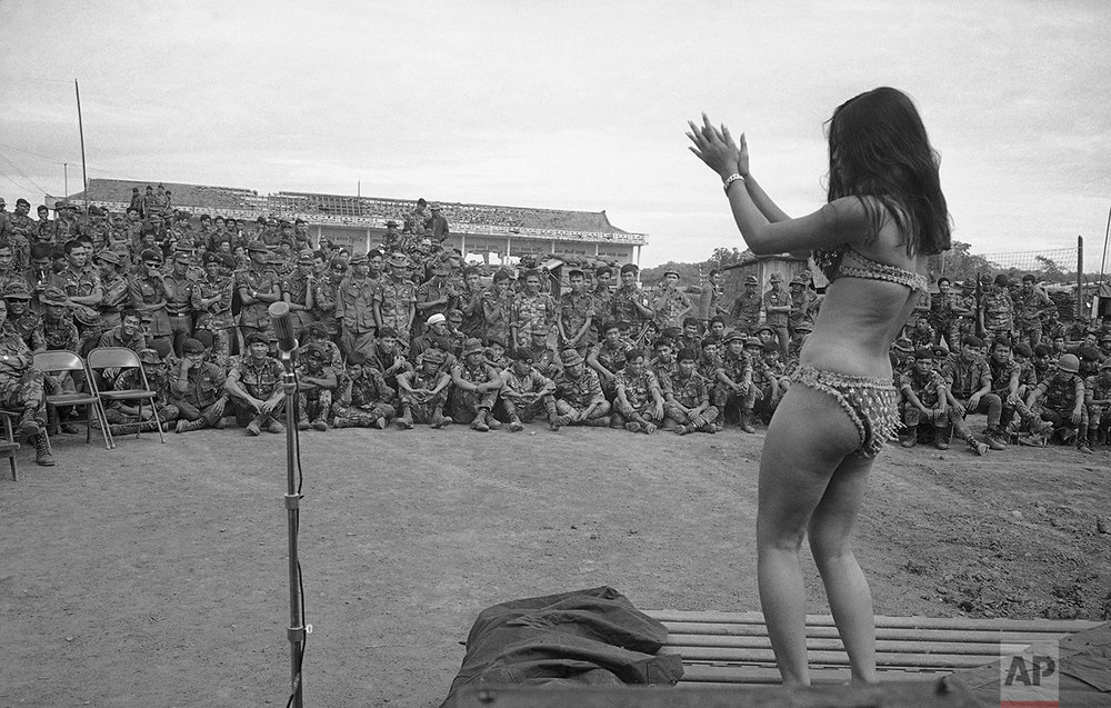 South Vietnamese troops take a break from their Cambodian operation to watch a dancer from Saigon perform at their base camp near Krek, Cambodia on Nov. 25, 1971. (AP Photo/Nick Ut)
