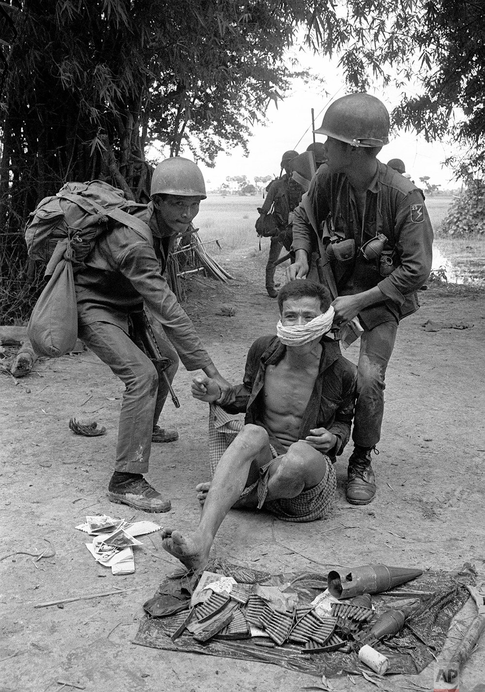 South Vietnamese ARVN soldiers restrain a Khmer Rouge suspect captured near ammunition in a Cambodian village on July 30, 1971.  The suspect was taken to ARVN headquarters for questioning.  (AP Photo/Nick Ut)