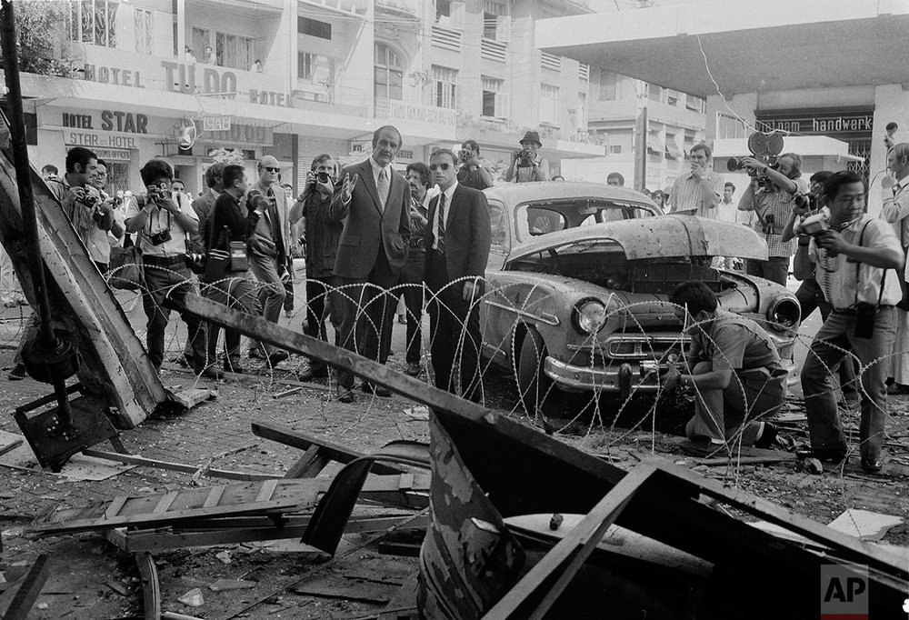 Senator George S. McGovern, center, gestures behind barbed wire barricade as he views the wreckage of a bombed nightclub in downtown Saigon, Sept. 16, 1971.  Fifteen persons were killed and nearly 60 injured in the Wednesday bombing, the worst terrorist blast in the South Vietnam capital in more than six years.  (AP Photo/Nick Ut)