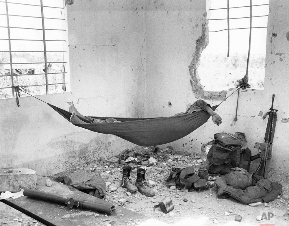 A South Vietnamese Marine naps in a hammock in an abandoned house in Quang Tri City, Vietnam, on August 24, 1972, his weapons and equipment nearby. (AP Photo/Nick Ut)