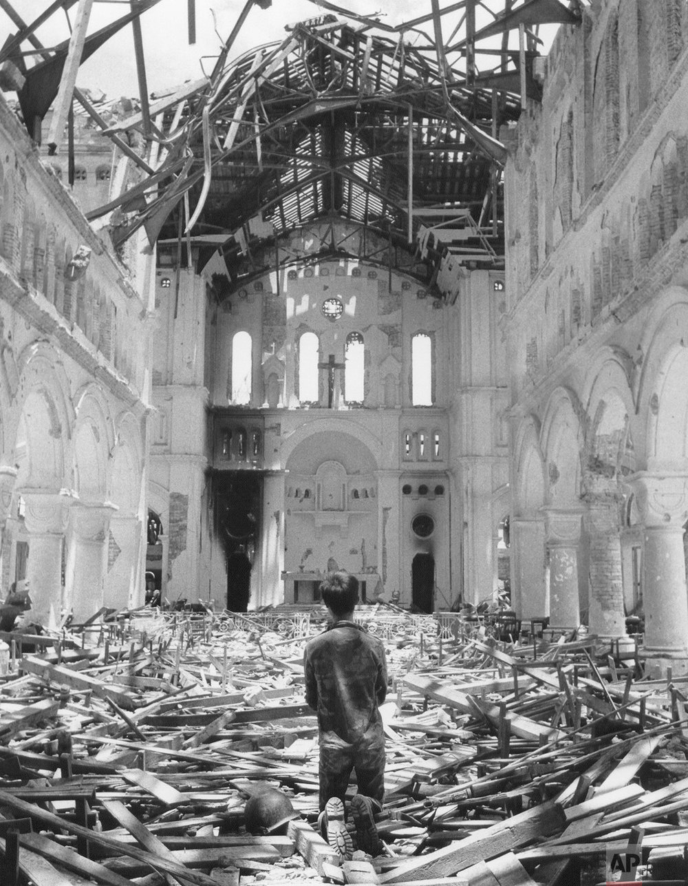 A South Vietnamese soldier kneels in prayer amid the ruins of the cathedral in La Vang, South Vietnam, on July 8, 1972 after government troops reentered the area near Quang Tri. The cathedral was damaged in fighting when the city fell to the North Vietnamese on May 1. (AP Photo/Nick Ut)